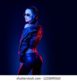 Sensual techno dancer woman in colorful club lighting.