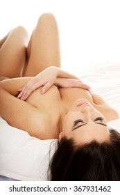 Sensual topless woman lying on bed.