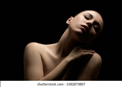 sensual topless young aroused woman with closed eyes on black background