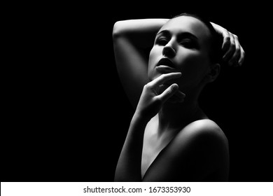 sensual topless young aroused woman with closed eyes on black background, monochrome