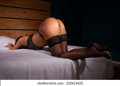 Sensual voluptuous woman with great ass in lingerie bend over on white bed in hotel room. Vulgar provocative shoot of doggy style position.