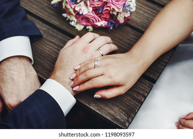 sensual wedding photo of a bridal couple holding hands next to a bouquet, groom and bride just happy together