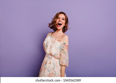 Sensual white woman in summer dress laughing on purple background. Charming female model in romantic clothes smiling during indoor photoshoot.