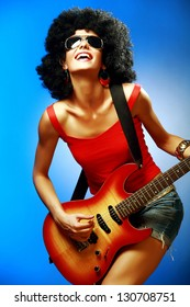 Sensual woman with afro hairstyle playing on the electric guitar against blue background