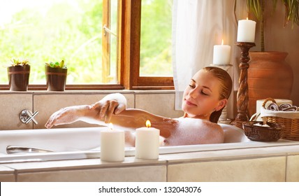 Sensual woman in bathtub relaxed, female in jacuzzi, taking bath, luxury spa resort, girl enjoying bathing with soap foam, vacation and holidays concept