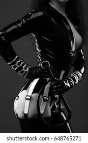 Sensual woman in black latex costume with riding crop