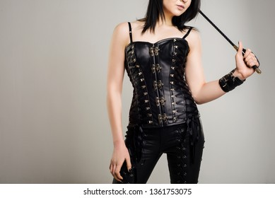 Sensual woman in black leather corset with riding crop in hand - image