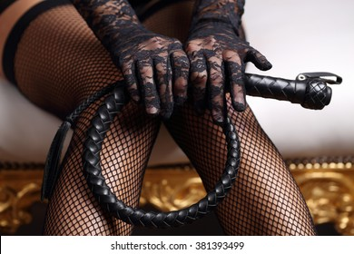 Sensual woman in black lingerie and leather whip