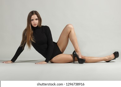 sensual woman in black turtleneck and black shoes lying in white background