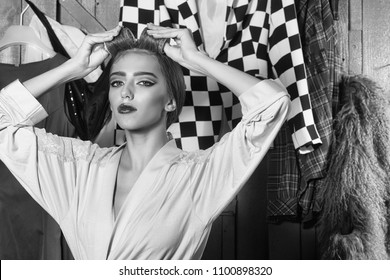 Sensual woman body. Closeup view of one beautiful young sensual housewife woman in dressing gown with hair-rollers on head standing in wardrobe among many bright clothes with raised hands, horizontal