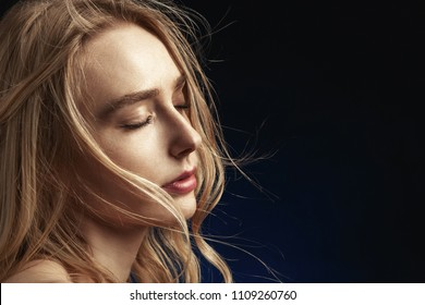 sensual woman with closed eyes and bare shoulders on black background with copy space