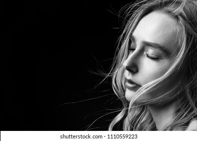 sensual woman with closed eyes and bare shoulders on black background with copy space, monochrome