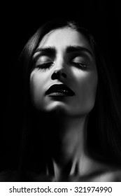 sensual woman with closed eyes in dark, monochrome