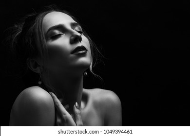 sensual woman, closed eyes on black background with copy space looking up, monochrome