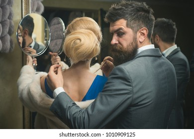Sensual woman in fur, man help fit pearl jewelry, shopping. Fashion, beauty, valentines day. Date, couple, love, man, woman. Couple in love on romantic date, relationship. Luxury, moneybags, business.