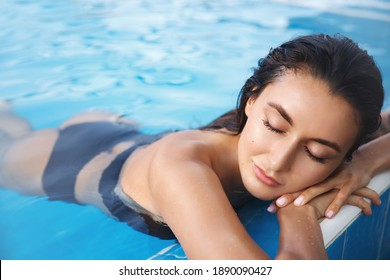 Sensual woman with golden tan, relaxing in spa swimming pool of tropical hotel resort, lying in water near poolside in black bikini, enjoying vacation.