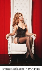 sensual woman in lingerie sitting on throne