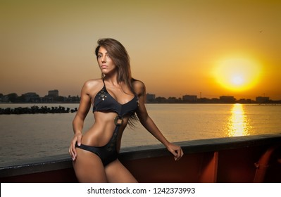 sensual woman with long hair and long legs and high heels in black bathing suit posing at sunset on a fishing boat.Sexy woman with beautiful breasts leans on a ship's railing at sunset