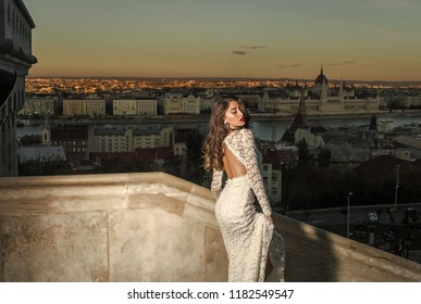 Sensual woman with long hair on balcony, beauty. Woman in white wedding dress on evening city view, fashion. Bride with makeup. Fashion model style and hairstyle. Girl with glamour look.
