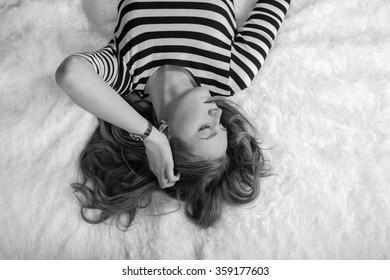 sensual woman lying on white fur, monochrome image