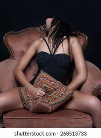 Sensual woman masturbating sitting on an armchair and