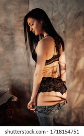 Sensual woman model posing in a soft sunlight of the apartment, wearing black lace lingerie and taking her jeans off her buttocks