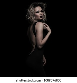 sensual woman in open back dress posing on side while touching her shoulder, standing on black background
