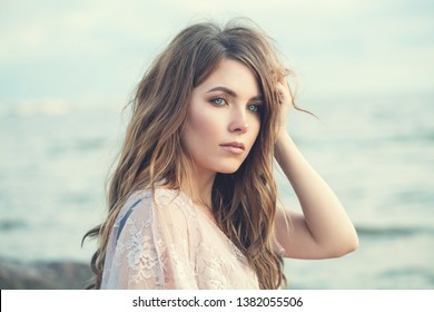 Sensual woman outdoor. Beautiful model girl with long curly brown hair on ocean background