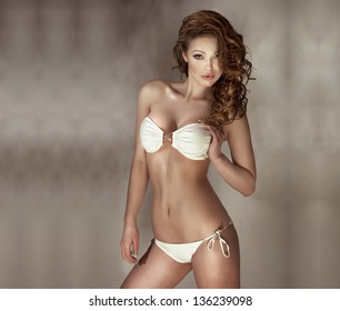 Sensual woman with perfect body wearing fashionable white swimwear posing, looking at camera. Long curly hair, beautiful breast.