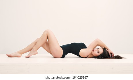 Sensual woman portrait laying on table with black underwear. Full body portrait.