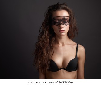 Sensual woman posing over dark background with lace mask on closed eyes