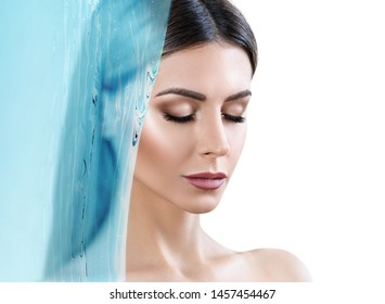 Sensual woman under water splash over white background. Cleansing and moisturizing concept.