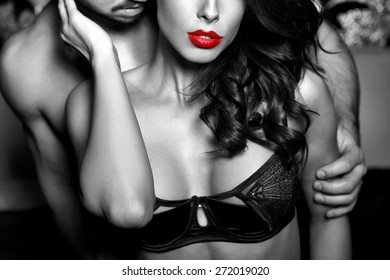 Sensual woman in underwear with young lover, passionate couple foreplay closeup, black and white, selective coloring
