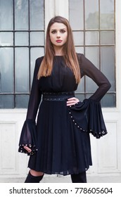 Sensual woman wearing a black dress in front of a white wall. Handsome lady in short fluttering dress with long sleeves and long black boots.