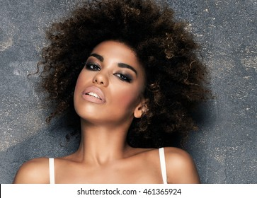 Sensual young african american girl posing in white underwear. Girl with afro and glamour makeup. Studio shot.
