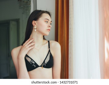 Sensual young beautiful long hair girl fashion model in underwear and jewerly accessorise near window in the room