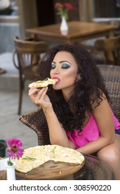Sensual young brunette lady with curly hair and bright makeup in pink clothes sitting in cafe outdoor eating hot delicious pizza with hands, vertical picture