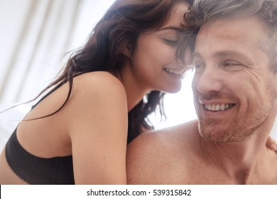 Sensual young couple together in bed. Happy couple in bedroom enjoying sensual foreplay.