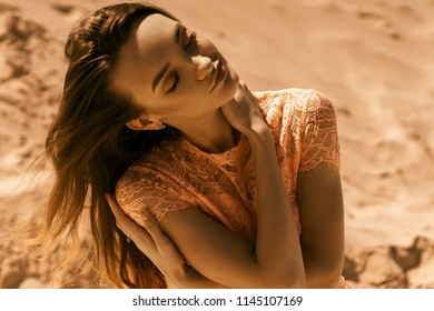 Sensual young girl with closed eyes outdoors in a desert