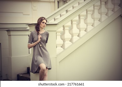 sensual young girl in fashion pose in outdoor location with elegant dress, stylish braid hair-style and cute jewellery