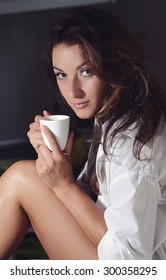 Sensual young girl sipping a cup of coffee