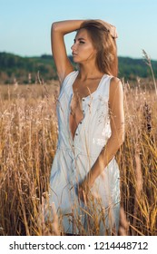 Sensual young girl with slim body standing and posing in the meadow in unbuttoned sleeveless jean sundress