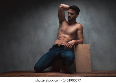 Sensual young guy kneeing and holding one of his hands on his head while wearing only jeans and leaning on a box, on gray studio background