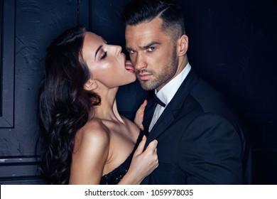 Sensual young lady licking her handsome, elegant lover