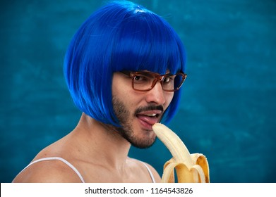 Sensual young male cross dressing person wearing blue wig and female cloth eats banana. Place for text.