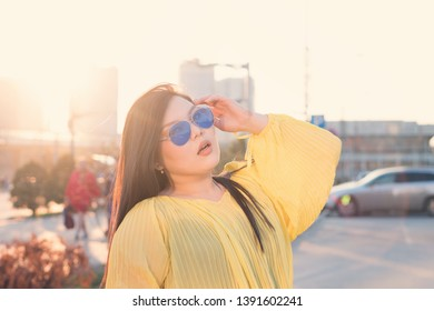 Sensual young plus size pan-asian girl posing in sunshine on city background. She plays with hair, straightens sunglasses, opens her mouth with puffy lips. Body positivity movement. Street fashion.