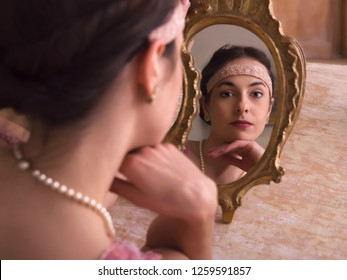 Sensual young woman in 1920s flapper dress and headband looking in an antique mirror