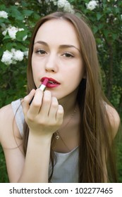 Sensual young woman applying cosmetics on her lips