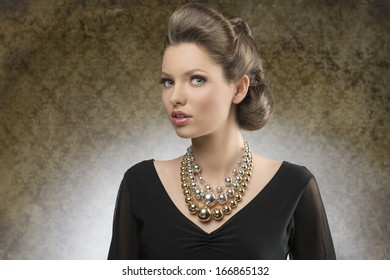 sensual young woman with brown creative hairdo posing in fashion shoot with black dress and bright big necklace