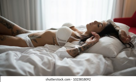 Sensual young woman close up portrait laying on her bed.